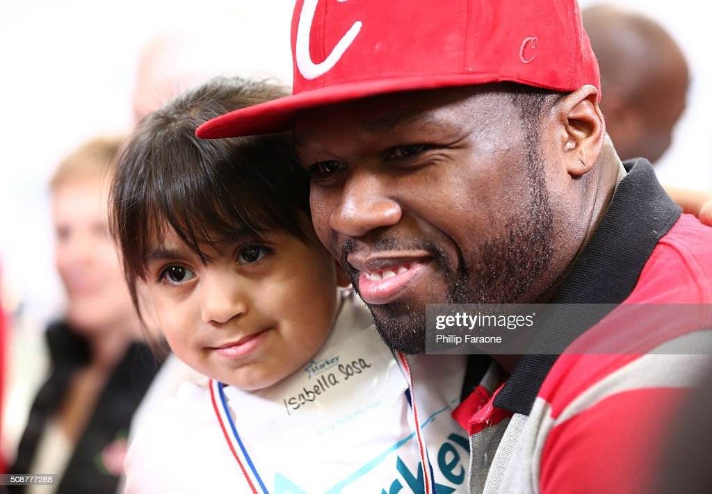 Rapper 50 Cent and patient Isabella look on during the Starkey Hearing Foundation hearing mission during Super Bowl weekend 2016 at San Francisco State University on February 6, 2016 in San Francisco, California.