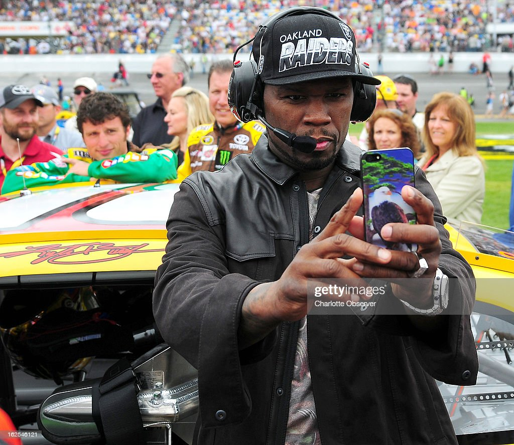 Rapper 50 Cent stands on pit road next to NASCAR Sprint Cup Series driver Kyle Busch's (18) car prior to the start of the Daytona 500 at Daytona International Speedway in Daytona Beach, Florida, Sunday, February 24, 2013.