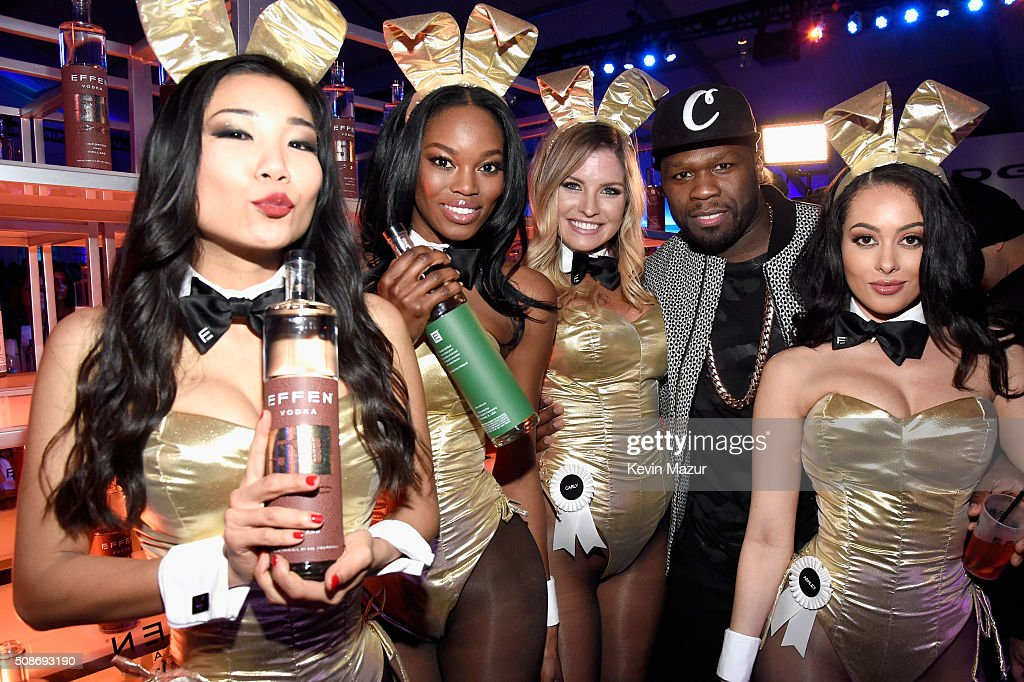 Rapper and entrepreneur 50 Cent (2nd from right) serves up his super-premium EFFEN Vodka at the The Playboy Party during Super Bowl Weekend with Playboy Playmates (L-R) Hiromi Oshima, Eugena Washington, Carly Lauren and Ashley Doris wearing Bunny costumes inspired by the gold detailing on his limited edition EFFEN Vodka football bottle. The Playboy Party celebrated the future of Playboy and its newly redesigned magazine in a transformed space within Lot A of AT&T Park on February 5, 2016 in San Francisco, California.