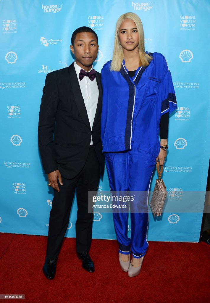 Rapper and music producer <a gi-track='captionPersonalityLinkClicked' href=/galleries/search?phrase=Pharrell+Williams&family=editorial&specificpeople=161396 ng-click='$event.stopPropagation()'>Pharrell Williams</a> (L) and model Helen Lasichanh arrive at the United Nations Foundation's 'mPowering Action' Innovative Mobile Platform launch party at The Conga Room at L.A. Live on February 8, 2013 in Los Angeles, California.