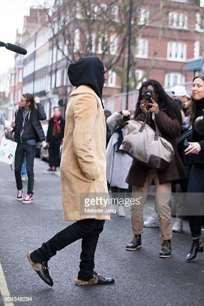 Rapper ASAP Rocky exits the JW Anderson show in a beige coat black hoodie and trousers and Gucci furlined loafers during The London Collections Men...