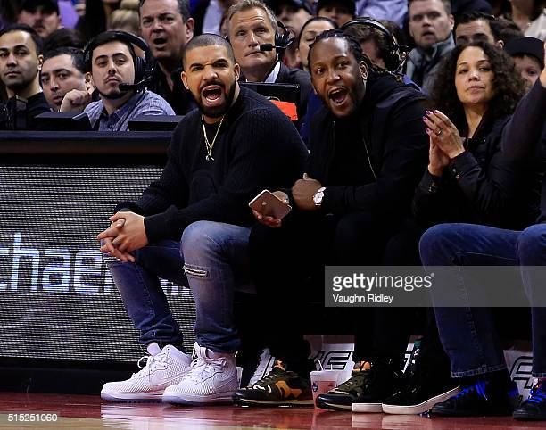 Rapper Drake shouts from his courtside seat during the second half of an NBA game between the Miami Heat and the Toronto Raptors at the Air Canada...