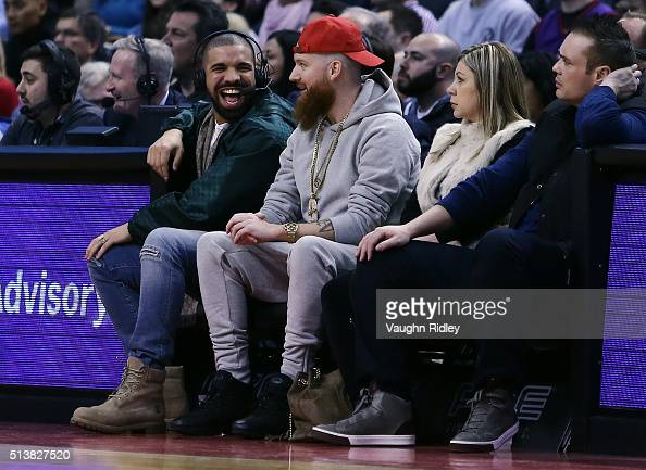 Rapper Drake smiles from his courtside seat during the first half of an NBA game between the Portland Trail Blazers and the Toronto Raptors at the...