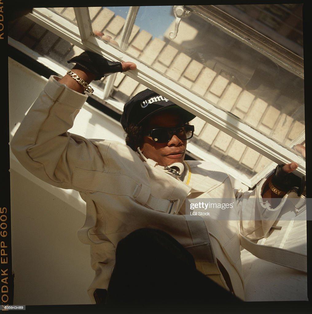 Rapper Eazy-E of the rap group, NWA, wears sunglasses, a black Compton baseball cap, and a straitjacket.