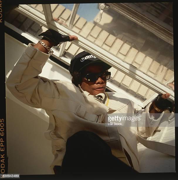 Rapper EazyE of the rap group NWA wears sunglasses a black Compton baseball cap and a straitjacket