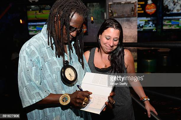 Rapper Flavor Flav signs a copy of his book 'Flavor Flav The Icon The Memoir' for a fan as he introduces his signature recipe 'Flavor Flav's Chicken'...