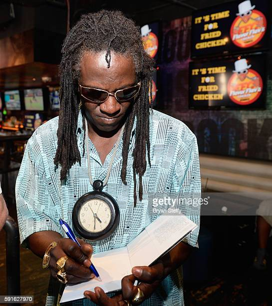 Rapper Flavor Flav signs a copy of his book 'Flavor Flav The Icon The Memoir' for fans as he introduces his signature recipe 'Flavor Flav's Chicken'...