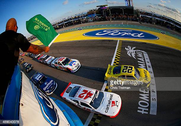 Rapper Flo Rida waves the green flag as Brad Keselowski driver of the Hertz Ford and Kyle Larson driver of the Cartwheel by Target Chevrolet lead the...