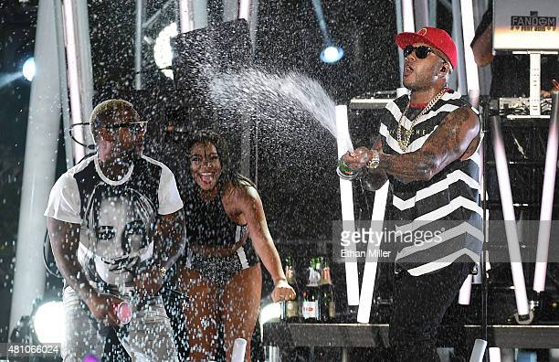 Rapper Gorilla Zoe and a dancer look on as rapper Flo Rida sprays sparkling wine on the crowd as they perform during the MTV Fandom Fest San Diego...