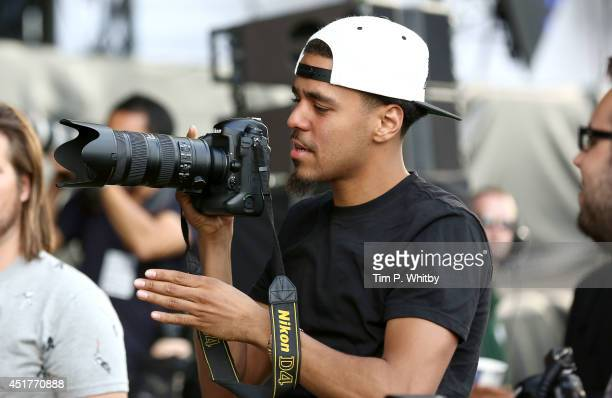 Rapper J Cole borrows a photographer's camera in the photo pit during the Outkast performance stage at Wireless Festival at Finsbury Park on July 6...