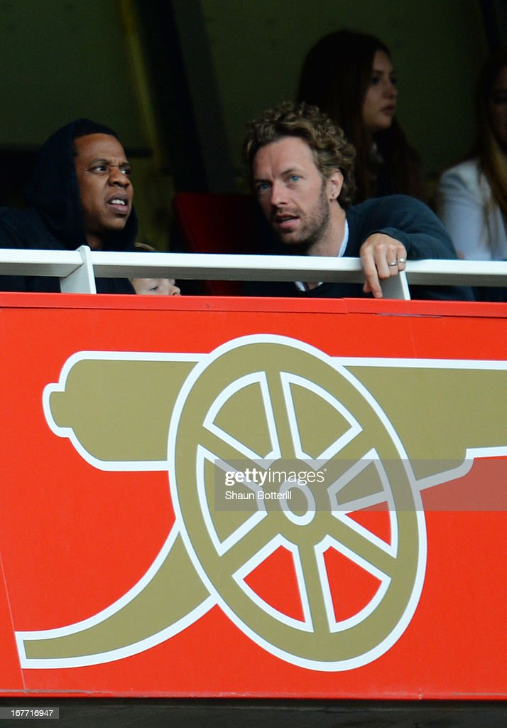 Rapper Jay-Z and Chris Martin of Coldplay look on during the Barclays Premier League match between Arsenal and Manchester United at Emirates Stadium on April 28, 2013 in London, England.