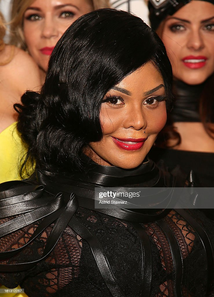 Rapper Lil' Kim poses for photos backstage at the Reality of FASHION the Reality of AIDS fall 2013 fashion show during Mercedes-Benz Fashion Week at the Altman Building on February 9, 2013 in New York City.