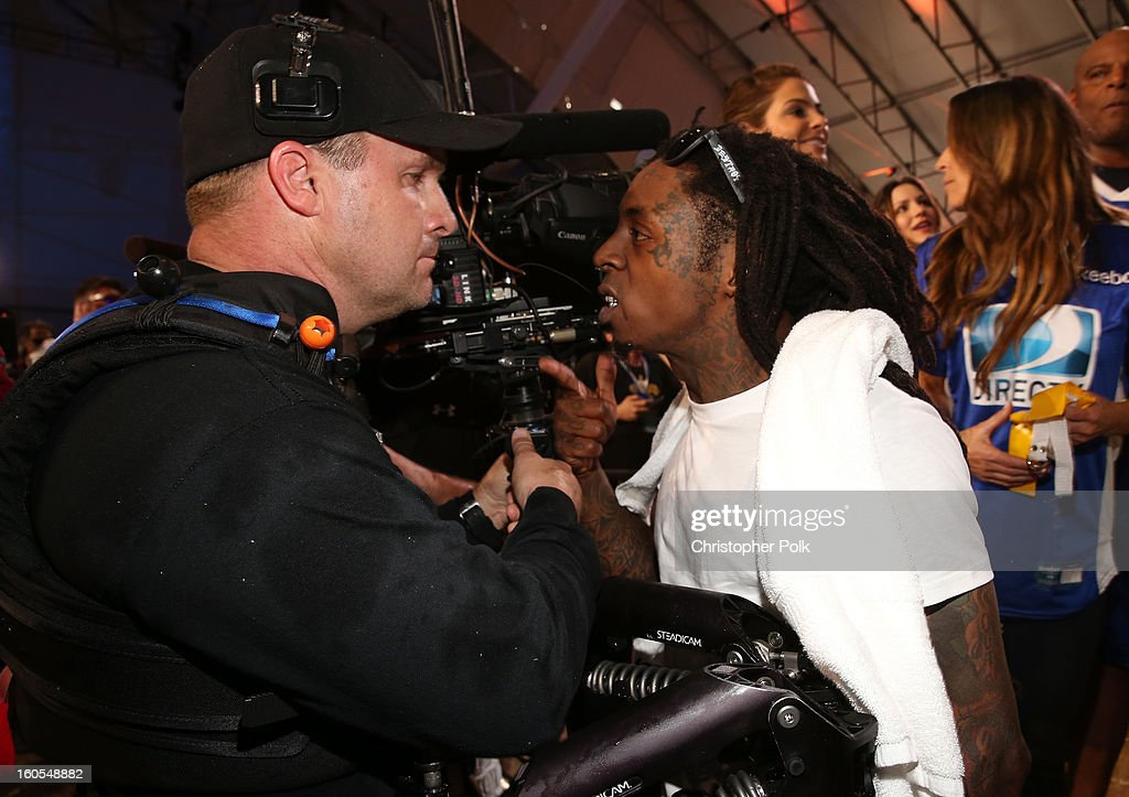 Rapper Lil Wayne (R) attends DIRECTV'S Seventh Annual Celebrity Beach Bowl at DTV SuperFan Stadium at Mardi Gras World on February 2, 2013 in New Orleans, Louisiana.