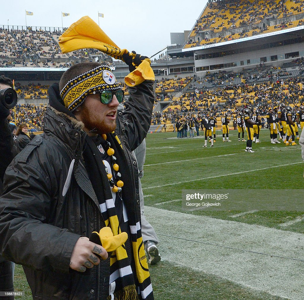 Rapper Mac Miller waves a Terrible Towel fom the sideline during player introductions before a National Football League game between the Cleveland Browns and Pittsburgh Steelers at Heinz Field on December 30, 2012 in Pittsburgh, Pennsylvania. The Steelers defeated the Browns 24-10.
