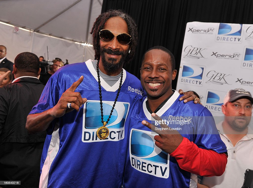 Rapper Snoop Dogg and Desmond Howard attend GBK and DirecTV Celebrity Beach Bowl Thank You Lounge at DTV SuperFan Stadium at Mardi Gras World on February 2, 2013 in New Orleans, Louisiana.