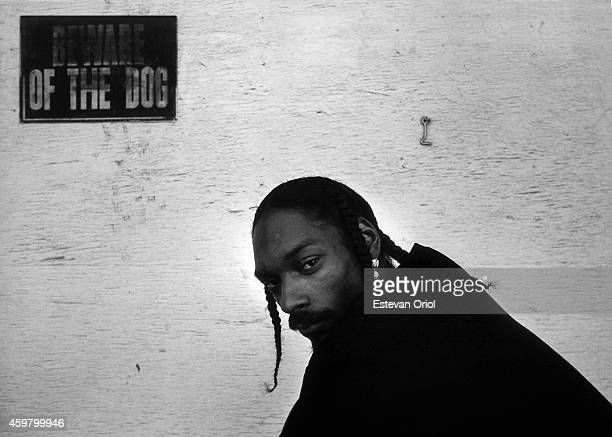 Rapper Snoop Dogg poses for a portrait session underneath a sign that warns 'Beward Of The Dog' in an alley oustide of Encore Studios in 1998 in...