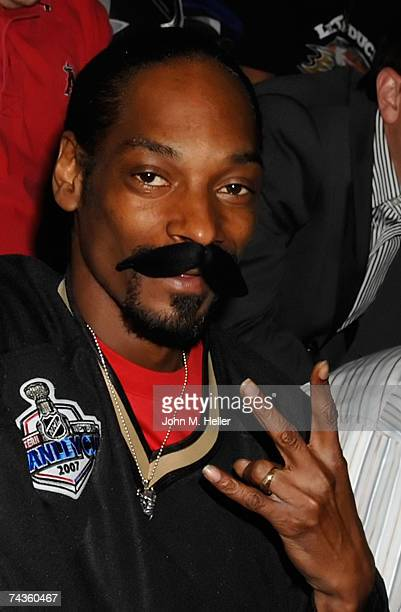 Rapper Snoop Dogg poses with a fake mustache as a tribute to George Parros of the Anaheim Ducks during Game Two of the 2007 NHL Stanley Cup Finals...