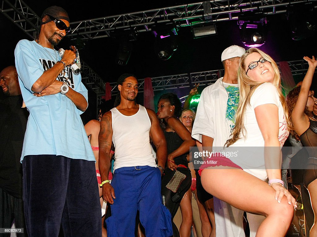 Rapper Snoop Dogg (L) watches girls dance on stage as he performs at the Kandy Vegas lingerie party at the Palms Casino Resort early July 26, 2009 in Las Vegas, Nevada.