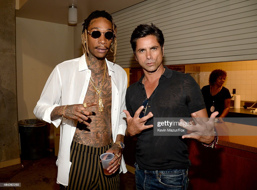 Rapper Wiz Khalifa and actor John Stamos attend the Teen Choice Awards 2015 at the USC Galen Center on August 16 2015 in Los Angeles California