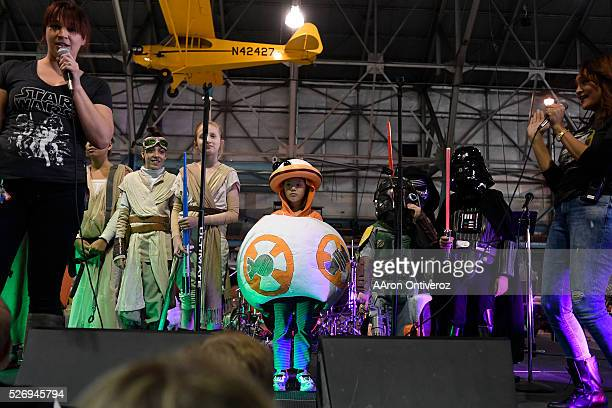 Raquel Bickford dressed as BB8 stands with other contestants in the children's costume contest before winning the title and a new lightsaber during a...