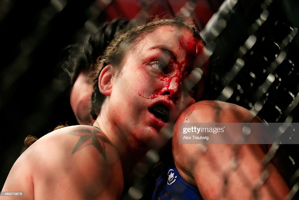 Raquel Pennington and Ashlee EvansSmith grapple against the cage in their fight during the UFC 181 event at the Mandalay Bay Events Center on...