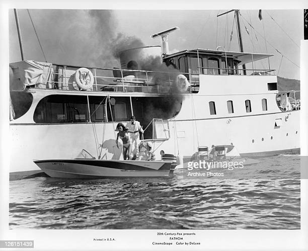 Raquel Welch And unknown actor race off burning boat onto speed boat in a scene from the film 'Fathom' 1967