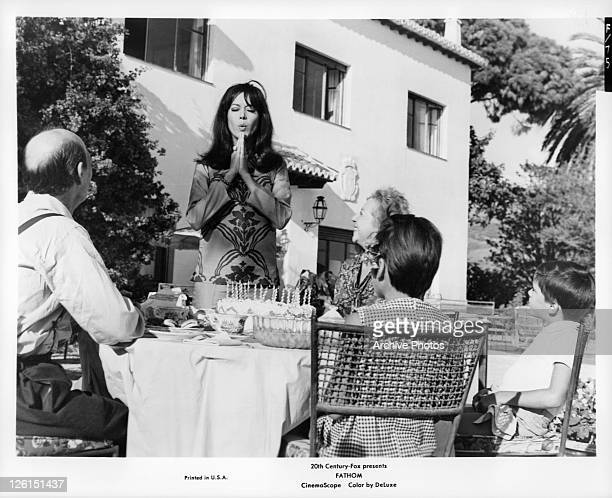 Raquel Welch praying over birthday cake in a scene from the film 'Fathom' 1967