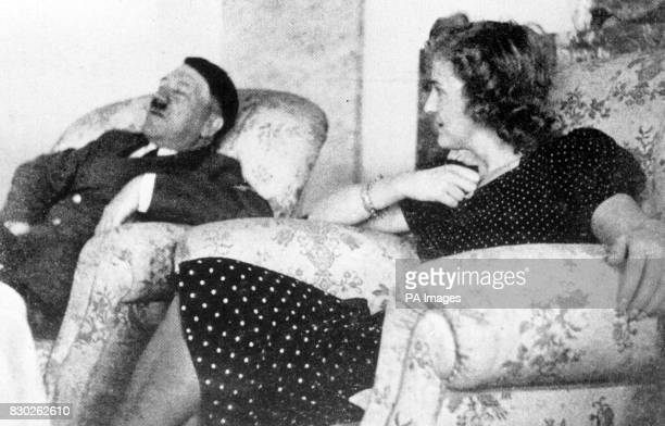 A rare archive picture of Adolf Hitler dozing in an armchair at his Berghof alpine residence in Bavaria with his mistress Eva Braun c1936