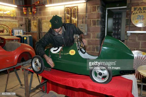 A rare Austin Pathfinder racing pedal car is cleaned by a fair ground worker at restorers Carters Steam Fair yard in White Waltham near Maidenhead...