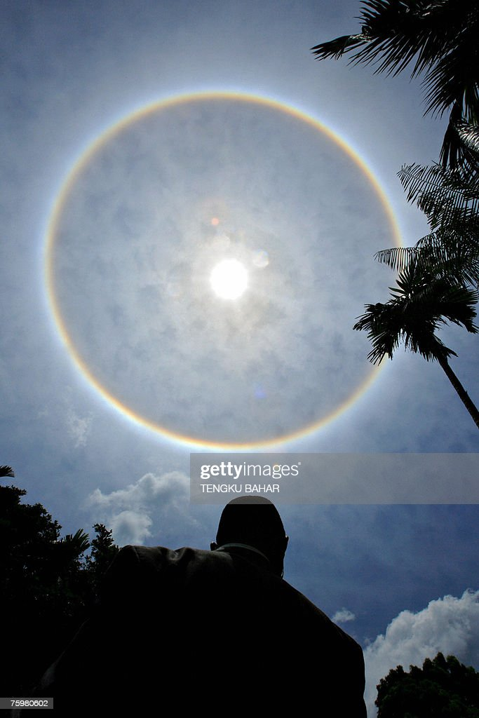 A rare full-circle rainbow surrounds a midafternoon sun as an African delegate (bottom), attending the 2007 Langkawi International Dialogue between African and Asian leaders, waits for his transport at the tropical island of Langkawi, northern Kedah state, 06 August 2007. A rainbow's appearance is caused by the dispersion of sunlight as it passes through water droplets, creating a colour spectrum of red, orange, yellow, green, blue, indigo and violet.