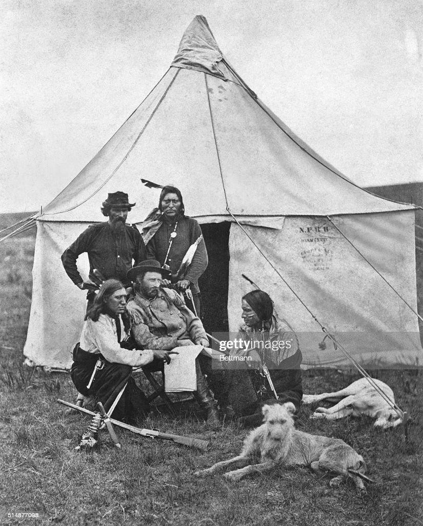 A rare print made in the early 1870's in Montana territory, showing General George A. Custer and some of his scouts when the General was in command of troops detailed to guard surveying and building crews constructing the Northern Pacific. The Indian standing by the tnet door is thought to be Curly, recorded as the only survivor of the Battle of the Little Bighorn where Custer's entire command was wiped out by the allied Indian tribes under Sitting Bull on June 26, 1876. It is interesting to note, also, that the tent bears the stamp of 'N.P.R.R.,' undoubtedly part of the equipment furnished Custer by the railroad.