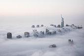 Rare winter morning fog blanketing Dubai skyscrapers in the Marina district.