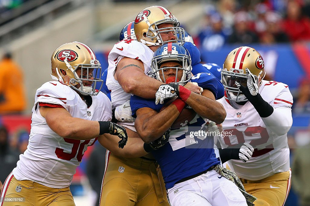 Rashad Jennings #23 of the New York Giants gets tackled by Glenn Dorsey #90, Quinton Dial #92 and Justin Smith #94 of the San Francisco 49ers at MetLife Stadium on November 16, 2014 in East Rutherford, New Jersey.