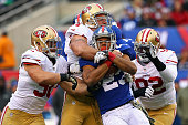Rashad Jennings of the New York Giants gets tackled by Glenn Dorsey Quinton Dial and Justin Smith of the San Francisco 49ers at MetLife Stadium on...