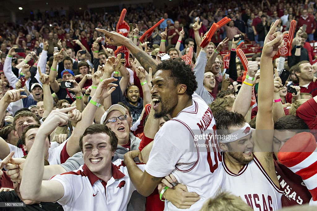 Rashad Madden #00 of the Arkansas Razorbacks celebrates with the student section after a game against the Florida Gators at Bud Walton Arena on February 5, 2013 in Fayetteville, Arkansas. The Razorbacks defeated the Gators 80-69.