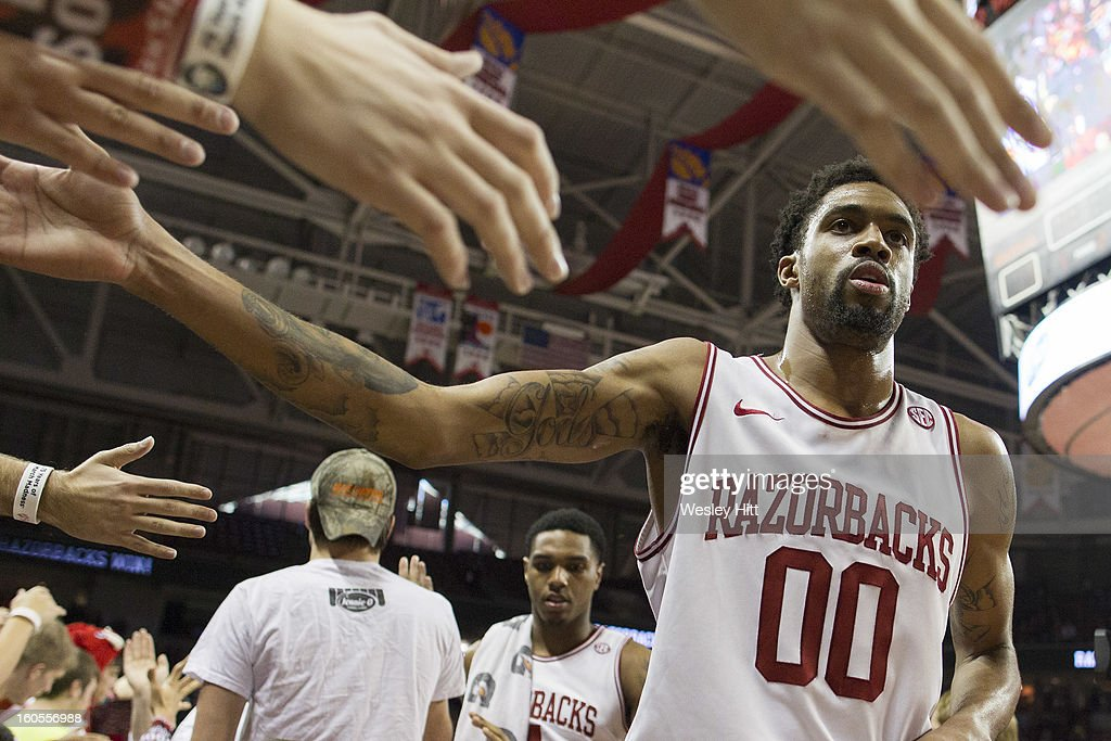 Rashad Madden #00 of the Arkansas Razorbacks slaps hands with fans after a game against the Tennessee Volunteers at Bud Walton Arena on February 2, 2013 in Fayetteville, Arkansas. The Razorbacks defeated the Volunteers 73-60.