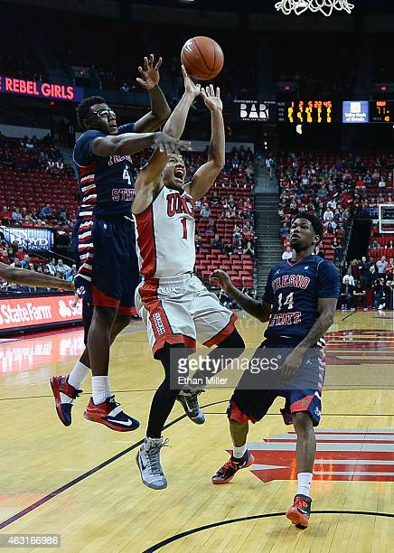 Rashad Vaughn of the UNLV Rebels is fouled as he drives to the basket against Karachi Edo and Julien Lewis of the Fresno State Bulldogs during their...