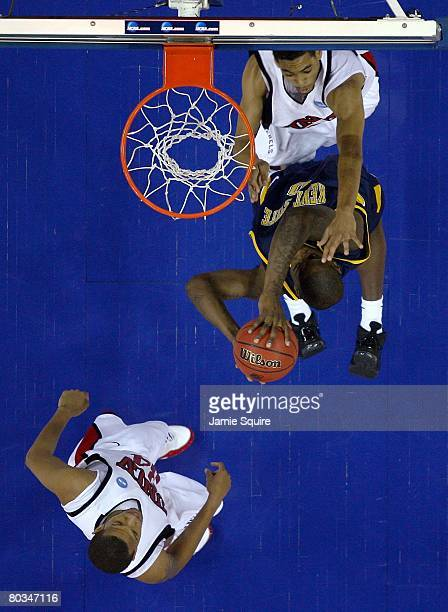 Rashad Woods of the Kent State Golden Flashes drives for a shot attempt against Rene Rougeau and Matt Shaw of the UNLV Runnin' Rebels during the...