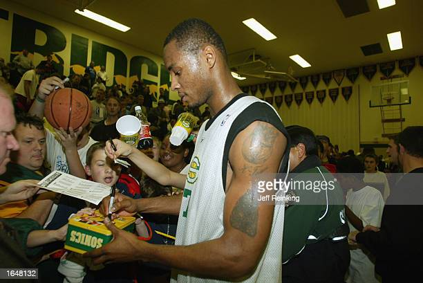 Rashard Lewis of the Seattle Sonics gives autographs to fans during the open practice at Kentridge High School on October 25 2002 in Seattle...
