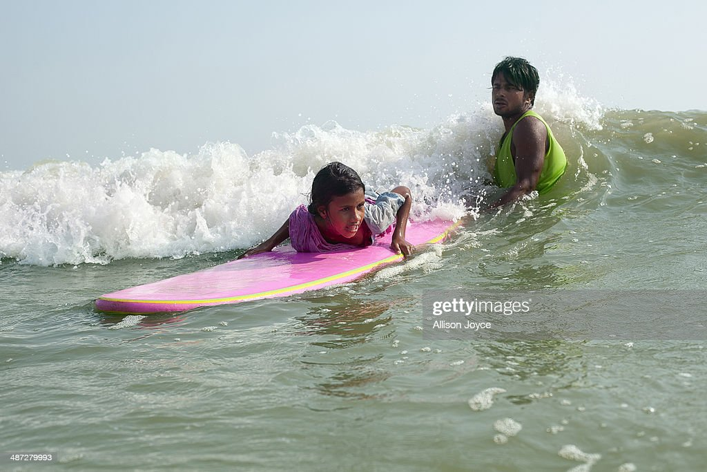 COX'S BAZAR, BANGLADESH - APRIL 15: Rashed Alam teaches 12 year old Shobhemeheraj to surf April 15, 2014 in Cox's Bazar, Bangladesh. A group of 10-12 year old female beach vendors, most of whom have dropped out of school to help support their families, have been learning to surf for the past three months in preparation for the annual Cox's Bazar surf competition. 24 year old surfer, lifeguard and beach worker Rashed Alam, has been teaching and mentoring the girls for 3 months. Like the girls, Alam dropped out of school and started working on the beach to help support his family at a young age. He started surfing when he was 16. He says that his way of giving back is by ensuring that girls get a good future through surfing.