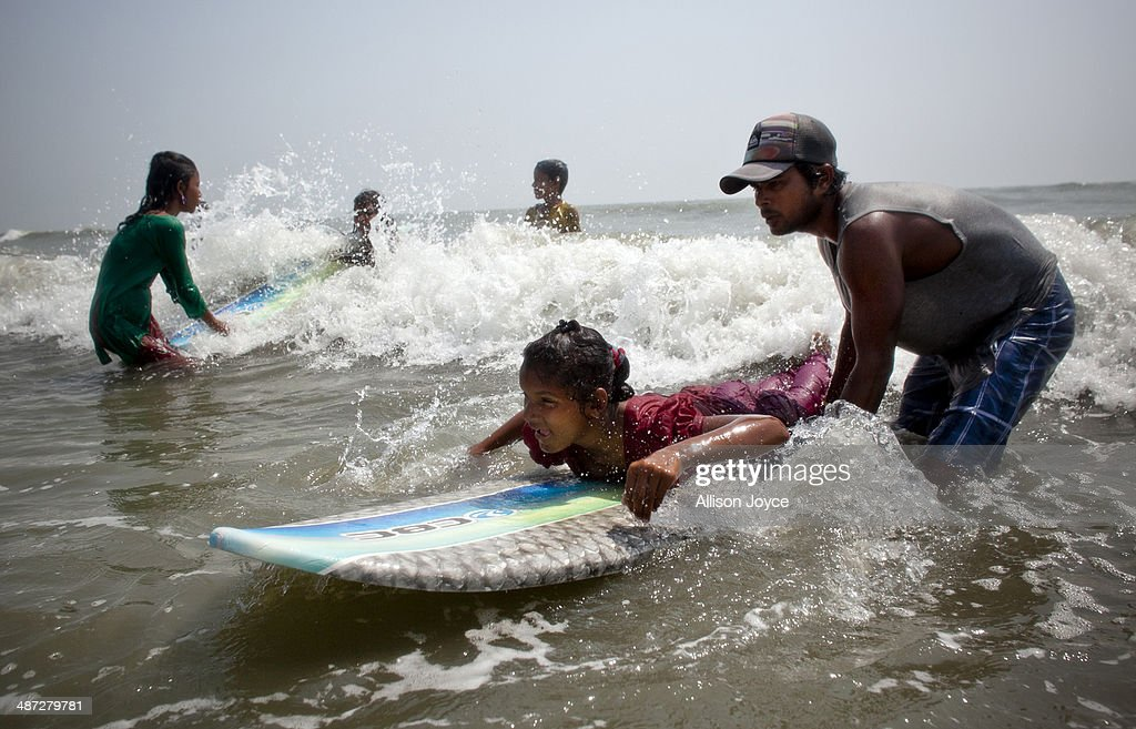 COX'S BAZAR, BANGLADESH - APRIL 12: Rashed Alam teaches 12 year old Shuma to surf April 12, 2014 in Cox's Bazar, Bangladesh. A group of 10-12 year old female beach vendors, most of whom have dropped out of school to help support their families, have been learning to surf for the past three months in preparation for the annual Cox's Bazar surf competition. 24 year old surfer, lifeguard and beach worker Rashed Alam, has been teaching and mentoring the girls for 3 months. Like the girls, Alam dropped out of school and started working on the beach to help support his family at a young age. He started surfing when he was 16. He says that his way of giving back is by ensuring that girls get a good future through surfing.