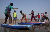 COX'S BAZAR BANGLADESH APRIL 15 Rashed Alam teaches beach vendors to surf April 15 2014 in Cox's Bazar Bangladesh A group of 1012 year old female...