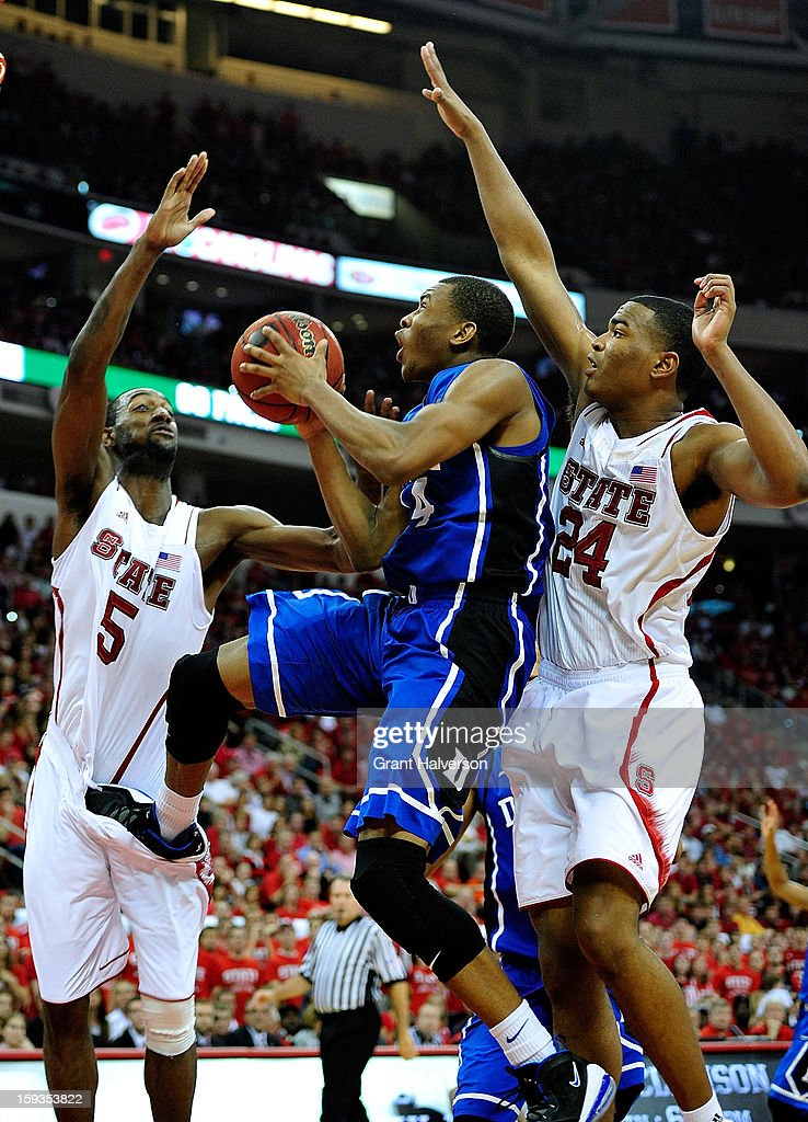 Rasheed Sulaimon #14 of the Duke Blue Devils drives between C.J. Leslie #5 and T.J. Warren #24 of the North Carolina State Wolfpack during play at PNC Arena on January 12, 2013 in Raleigh, North Carolina. North Carolina State won 84-76.