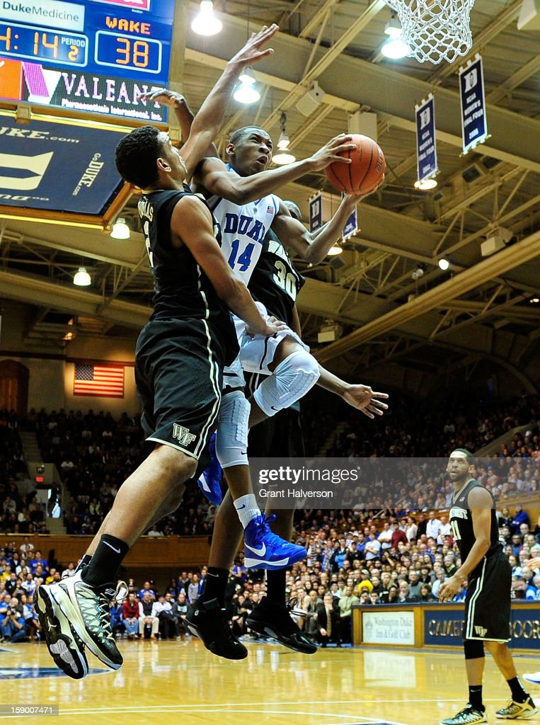 Rasheed Sulaimon #14 of the Duke Blue Devils drives between Devin Thomas #2 and Travis McKie #30 of the Wake Forest Demon Deacons during play at Cameron Indoor Stadium on January 5, 2013 in Durham, North Carolina. Duke won 80-62.