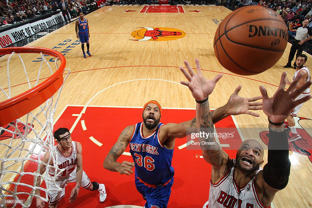 Rasheed Wallace #36 of the New York Knicks and Carlos Boozer #5 of the Chicago Bulls jump for the rebound on December 8, 2012 at the United Center in Chicago, Illinois.