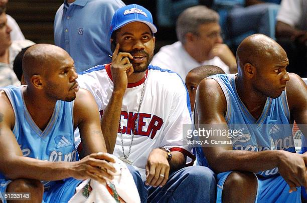 Rasheed Wallace talks on his cell phone while sitting on the bench with Jerry Stackhouse and Brendan Haywood during the World's Greatest Alumni Game...