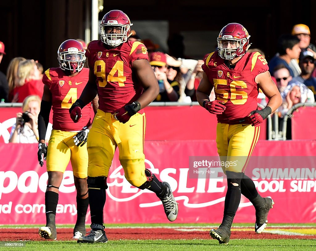 Rasheem Green #94 of the USC Trojans reacts with Anthony Sarao #56 to his touchdown from a fumble to take a 26-21 lead over the UCLA Bruins during the third quarter at Los Angeles Memorial Coliseum on November 28, 2015 in Los Angeles, California.