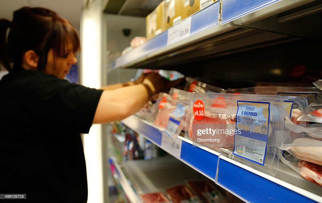Rashers of Tesco Plc own brand bacon sit in a refrigerated meat cabinet as an employee arranges meat products inside the Community shop, a supermarket for low-income families, in Goldthorpe, U.K., on Monday, Dec. 23, 2013. Company Shop Ltd. created the Community shop for people in, or bordering on, food poverty, selling surplus goods from major retailers at discounted prices. Photographer: Paul Thomas/Bloomberg via Getty Images