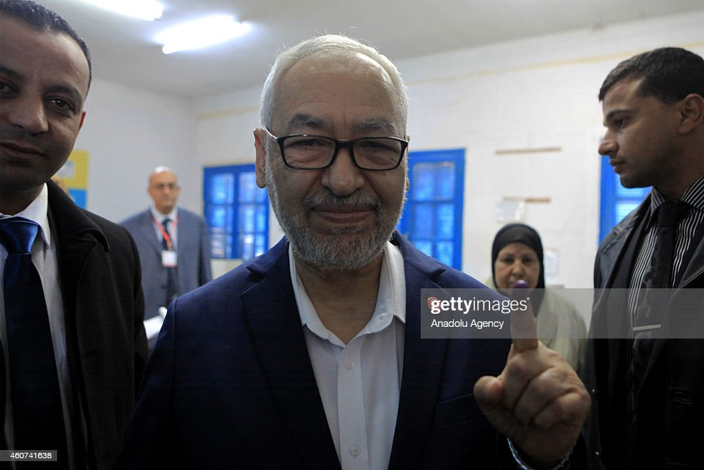 Rashid al-Ghannushi (C) leader of Ennahda Movement shows his inked finger after casting his vote at Nahc al-Keyrevan school during the second round of Tunisia's presidential election in Ben Arous, Tunis on December 21, 2014.
