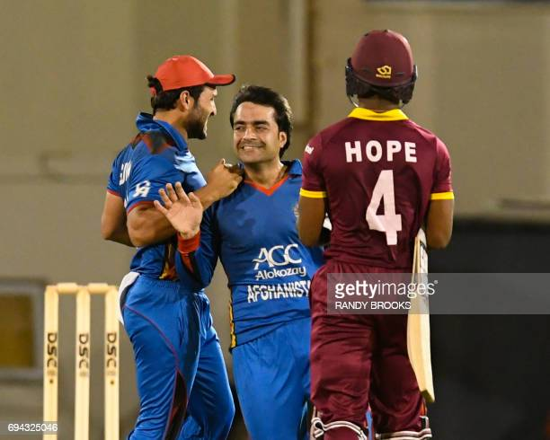 Rashid Khan and Gulbadin Naib of Afghanistan celebrate the dismissal of Shai Hope of West Indies during the 1st ODI match between West Indies and...